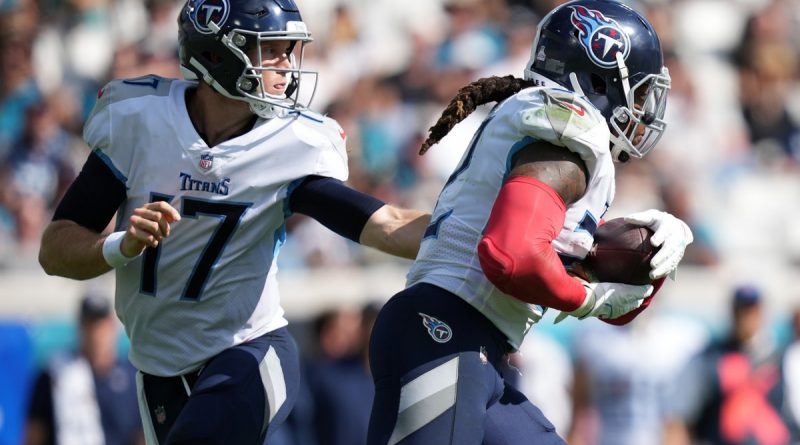Oct 10, 2021; Jacksonville, Florida, USA; Tennessee Titans quarterback Ryan Tannehill (17) hands the ball to running back Derrick Henry (22) during the second half against the Jacksonville Jaguars at TIAA Bank Field. Mandatory Credit: Jasen Vinlove-USA TODAY Sports